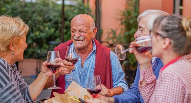 Groep oude mensen die buiten eten en drinken - senioren die buiten plezier hebben