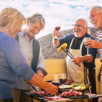 Groep oude senior mensen hebben weer plezier samen na lockdown eten en bbq doen