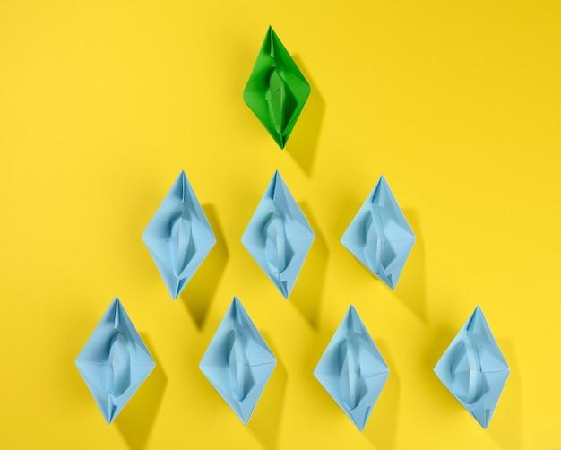 Groep papieren boten op een geel oppervlak. concept van een sterke leider in een team, manipulatie van de massa, het volgen van nieuwe perspectieven, samenwerking en eenwording. opstarten
