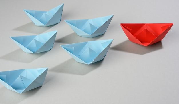 Groep papieren boten op een grijze achtergrond. concept van een sterke leider in een team, manipulatie van de massa, het volgen van nieuwe perspectieven, samenwerking en eenwording. opstarten