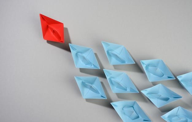 Groep papieren boten op een grijze ondergrond. concept van een sterke leider in een team, manipulatie van de massa, het volgen van nieuwe perspectieven, samenwerking en eenwording. opstarten