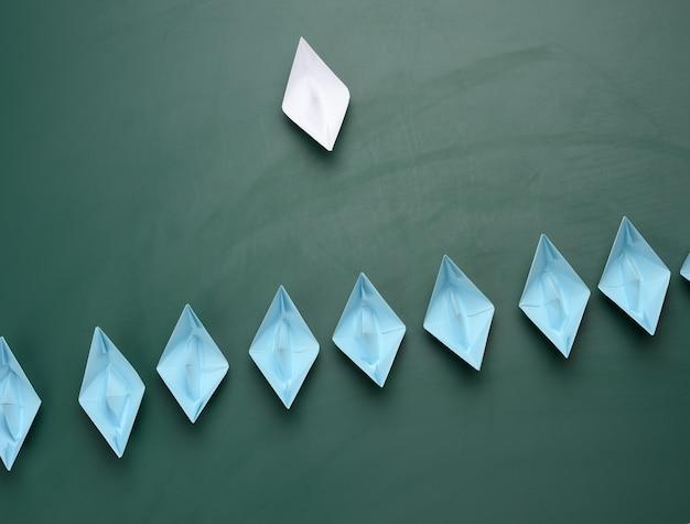 Groep papieren boten op een groene achtergrond. concept van een sterke leider in een team, manipulatie van de massa, het volgen van nieuwe perspectieven, samenwerking en eenwording. opstarten