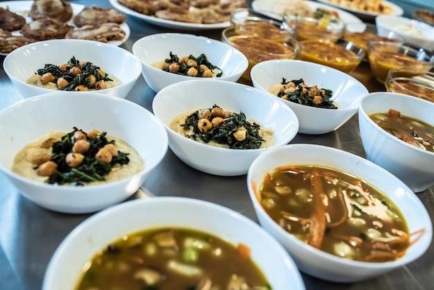Groep platen met soepen van verschillende soorten in hete kommen.