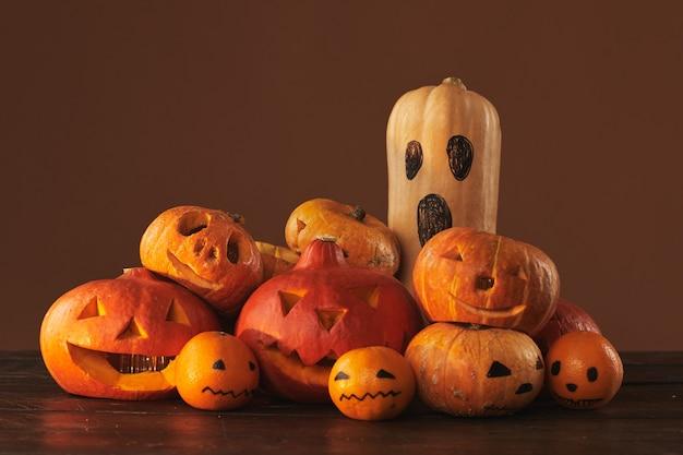 Groep pompoenen, kalebassen en mandarijnen gesneden en geschilderd voor halloween-feestdecoratie tegen bruin oppervlak