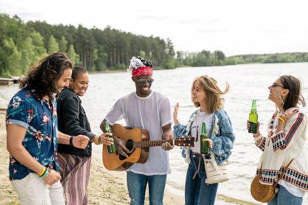 Groep positieve jonge multi-etnische vrienden dansen op strand onder gitaarmuziek door hippie zwarte man