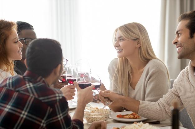 Groep positieve jonge multi-etnische vrienden zittend aan tafel en rammelende wijnglazen op diner
