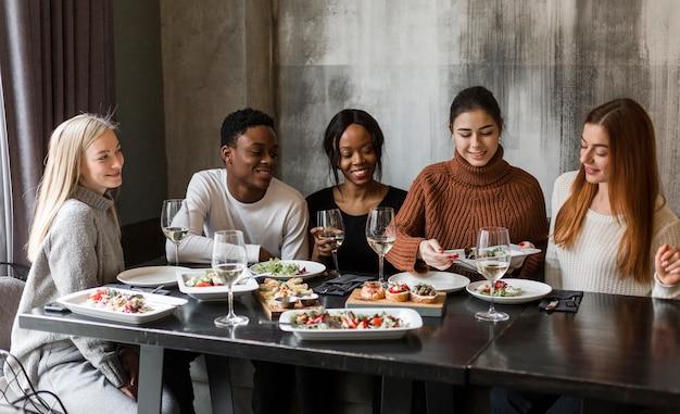 Groep positieve mensen die diner hebben samen