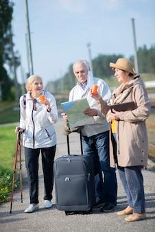 Groep positieve senior mensen kijken naar kaart op reis.