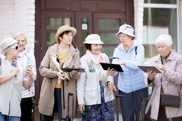Groep positieve senior oudere vrouwen kijken naar tablet op reis.