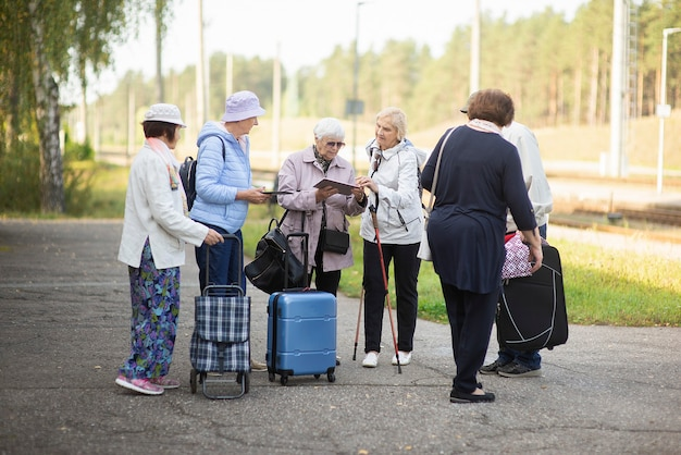 Groep positieve senior ouderen kijken naar digitale kaart op reis.