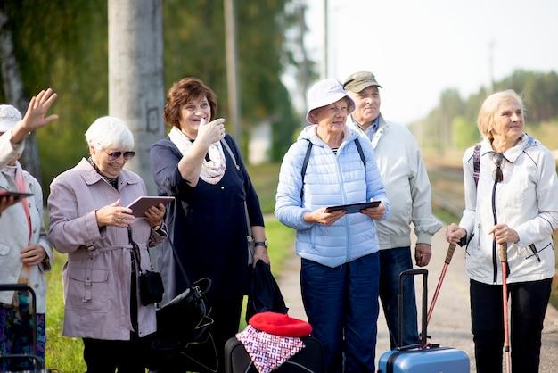 Groep positieve senior ouderen kijken naar tablet op reis.