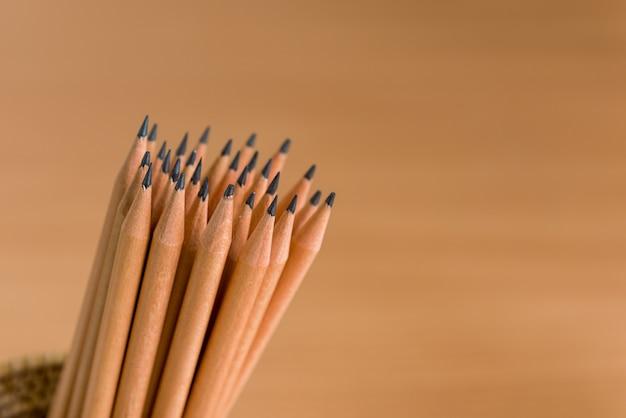 Groep potloden die zich op bruine achtergrond bevinden