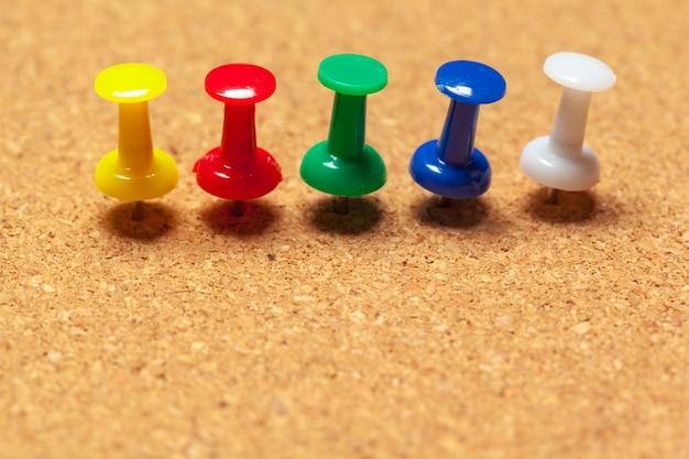 Groep punaises vastgemaakt op prikbord in rijen