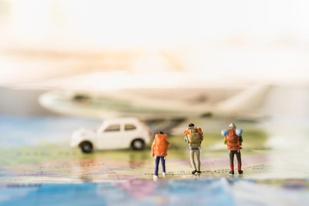 Groep reizigers miniatuur minicijfers met rugzak die op kaart aan vliegtuigmodel en witte stuk speelgoed auto lopen