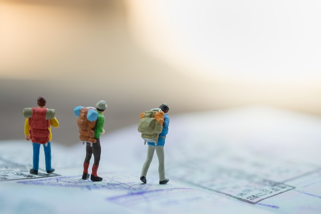 Groep reizigers miniatuurcijfers met rugzak die op paspoort met immigratiezegels loopt.