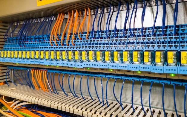 Groep relais op een rij in elektrokabinet van industrieel systeem van de automatiseringscontrole