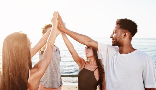 Groep riends die hun handen op het strand opheffen