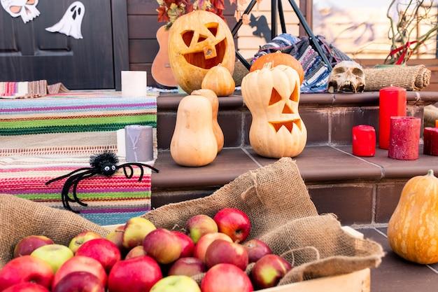 Groep rijpe halloween-pompoenen, spin, hoop appels, schedel, rode kaarsen op trap en andere spullen bij deur van landhuis