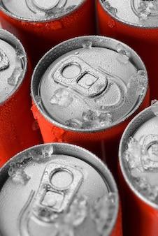 Groep rode aluminium blikjes frisdrank in ijs met waterdruppeltjes