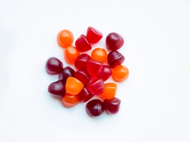 Groep rode, oranje en paarse multivitamine gummies geïsoleerd op een witte achtergrond. gezond levensstijlconcept.