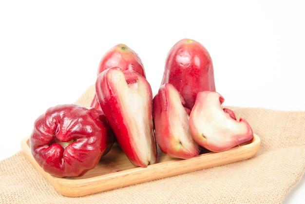 Groep roze appel of java appel op een houten dienblad op witte achtergrond.