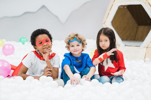 Groep schattige kleine interculturele vrienden in kostuums zitten onder witte ballonnen in de kinderkamer