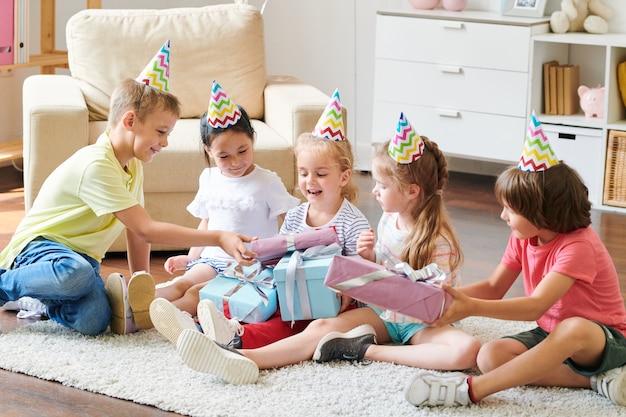 Groep schattige vrienden in verjaardag caps geven hun cadeautjes aan gelukkig blond meisje thuis feestje