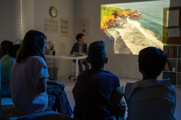 Groep schoolkinderen kijken naar video over natuurlijke omgeving in donkere klas