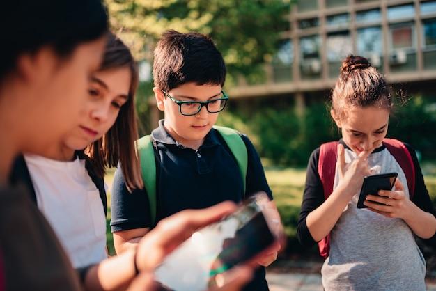 Groep schoolkinderen met behulp van slimme telefoons