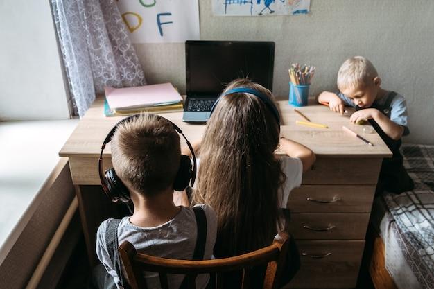 Groep schoolkinderen of vrienden die een koptelefoon dragen die in de buurt van een laptop zit, een schoolleerling thuis