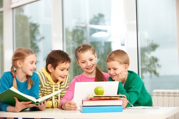 Groep schoolkinderen op zoek naar laptop in de klas