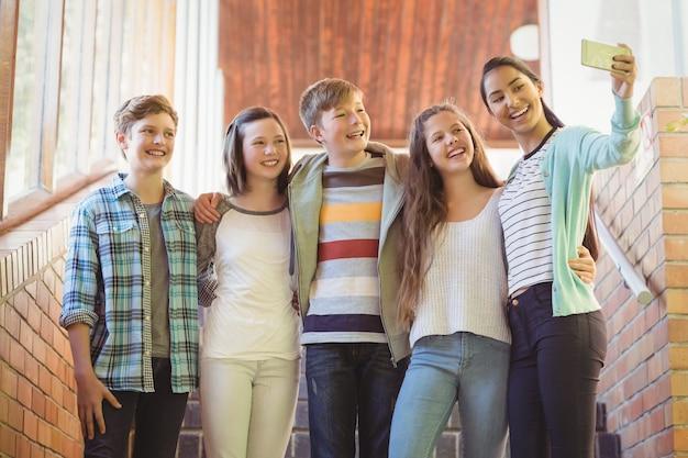 Groep schoolvrienden die selfie met mobiele telefoon nemen
