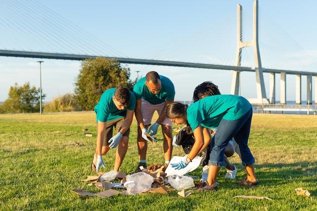 Groep schoonmakende arbeiders die afval in openlucht verzamelen