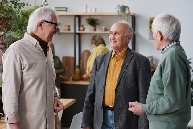 Groep senior mannen in pakken die met elkaar praten tijdens hun ontmoeting
