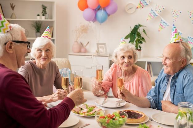 Groep senior mensen zitten door geserveerd tafel thuis tijdens het vieren van verjaardag