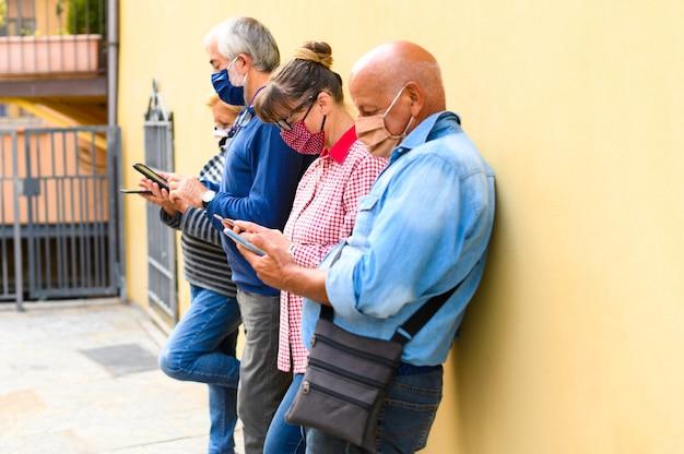 Groep senior vrienden kijken naar slimme mobiele telefoons