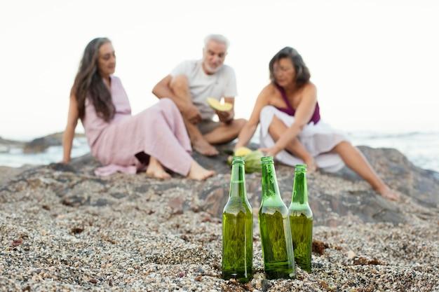Groep senior vrienden met bier op het strand