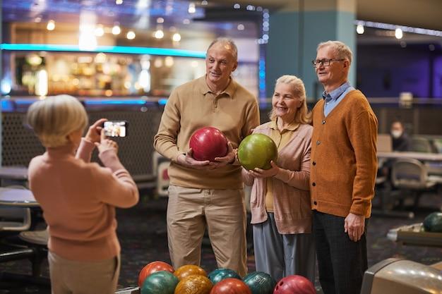 Groep senioren die foto's maken terwijl ze bowlen en genieten van actief entertainment op de bowlingbaan, kopieer ruimte