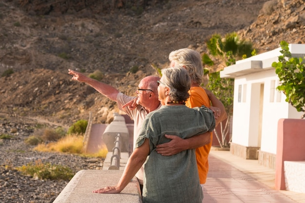 Groep senioren en volwassen mensen op het strand die naar de zee of de oceaan kijken omhelsd en een van hen geeft iets aan