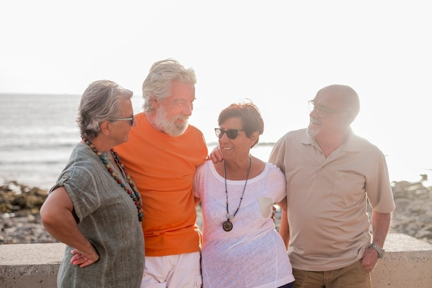 Groep senioren en volwassen mensen op het strand die samenkomen en plezier hebben met de zee of de oceaan op de achtergrond - vier personen