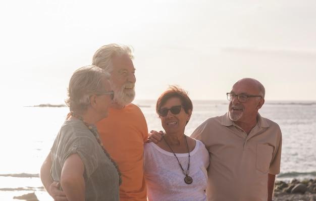 Groep senioren op het strand die samen praten en plezier hebben - gelukkige en volwassen paople in vriendschap of relatie met de zee of oceaan op de achtergrond