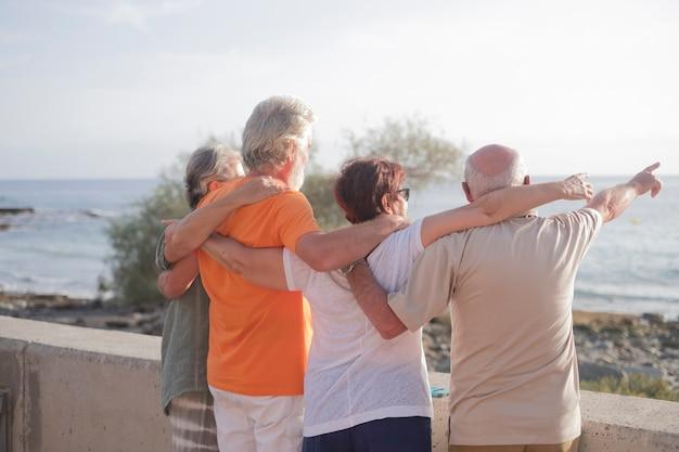Groep senioren samen omhelsd op het strand kijkend naar de zee met een prachtige zonsondergang - familie genieten op vakantie - man indicatie iets in de zee