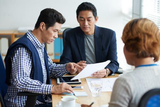 Groep serieuze zakenmensen die nieuwe ideeën bespreken tijdens briefingsessies en werken aan de ontwikkelingsstrategie