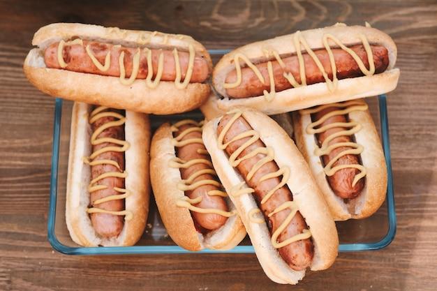 Groep smakelijke hotdogs met worstjes en mosterd
