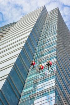 Groep specialisten die de glasvoorgevel van een wolkenkrabber schoonmaken, het risicovolle werk