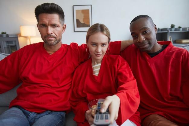 Groep sportfans die rood dragen terwijl ze thuis naar een wedstrijd kijken en de afstandsbediening vasthouden