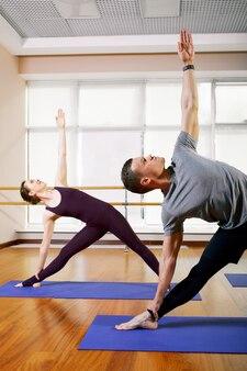 Groep sportieve mensen die op matten zitten en oefening voor ontspanning doen
