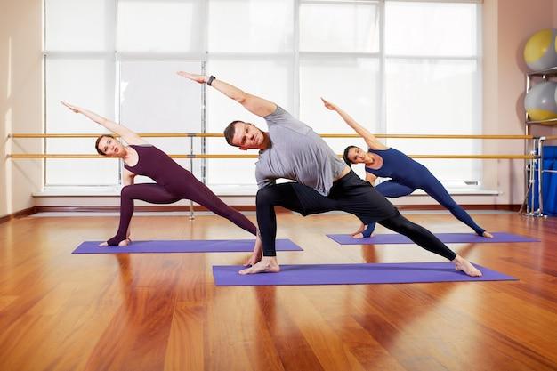 Groep sportieve mensen die op matten zitten en oefeningen doen voor ontspanning.