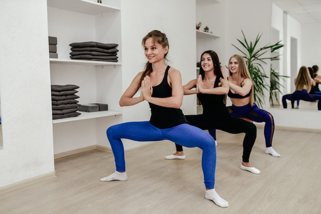 Groep sportieve mensen die yogales met instructeur uitoefenen