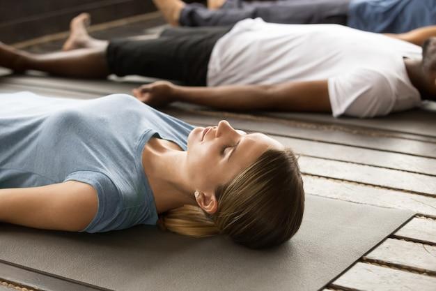Groep sportieve mensen in de oefening van het dode lichaam